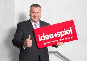 """idee+spiel Geschäftsführer Marketing, Andreas Schäfer präsentiert das neue Logo nebst """"Claim"""""""