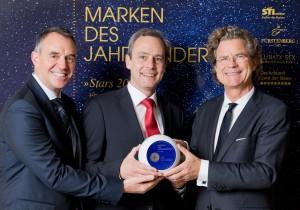 """Dr. Florian Langenscheidt (rechts) übergab den exklusiven Markenpreis für VEDES am 24. November 2015 an Wolfgang Groß (Mitte) und Stephan Bercher (links) Bildquelle """"Deutsche Standards/pjk-atelier"""""""